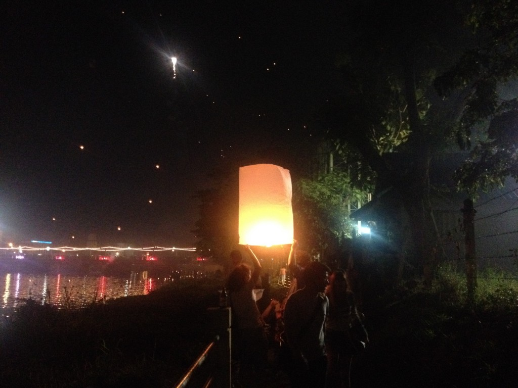 Tourists releasing a floating lantern by the Ping River