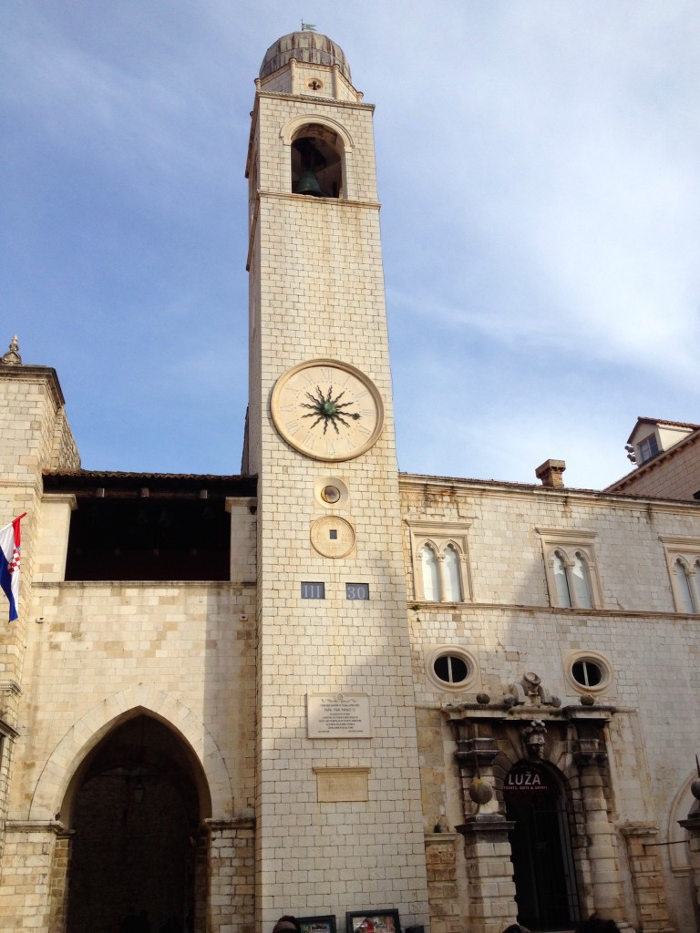 "Dubrovnik's Clock Tower. The golden circle below the main clock face shows the current phase of the moon. There's also a digital readout lower, showing the time, 3:30pm. First it has ""III"", roman numerals for 3, then 30 for the minutes."