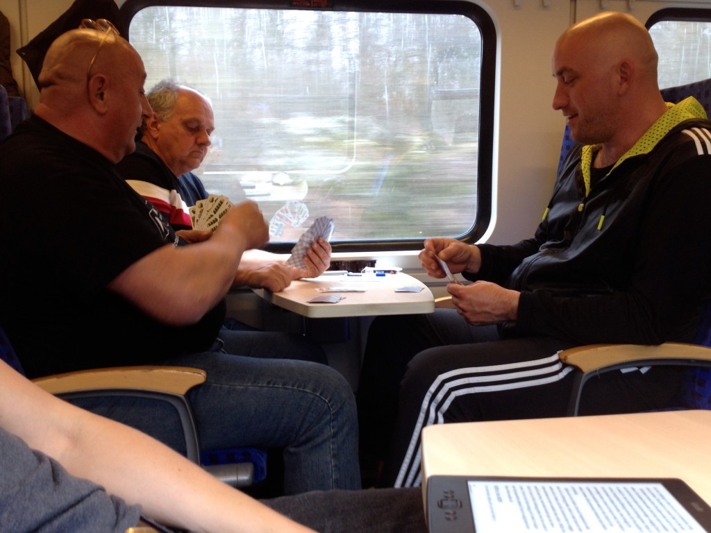 Folks on the train playing cards!
