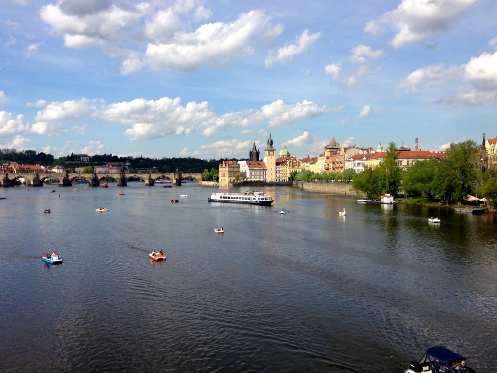 The beautiful Vltava River in Prague, with the stone arched Charles Bridge in the background.