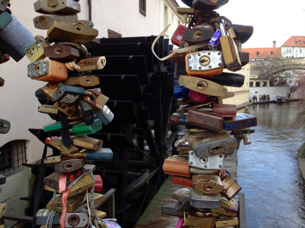 "An old water wheel in Prague's Little Quarter. Some people have used this bridge I was standing on as their own little ""lock bridge"" here in Prague. (Don't know what a lock bridge is? Lots of couples will write their initials on a lock and attach it to a bridge as a symbol of their love.)"